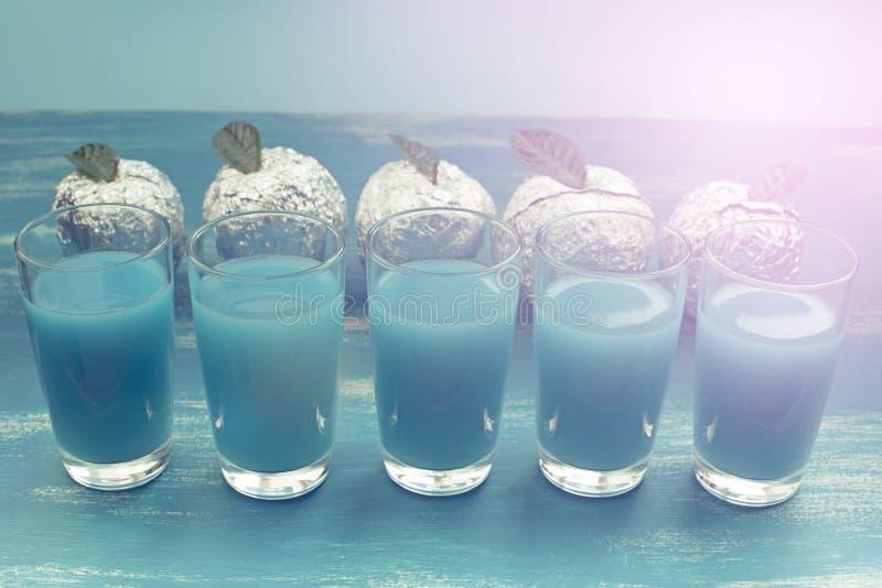 Cinco vidrios del surrealismo azul Apple de la bebida Foil el fondo lamentable azul imágenes de archivo libres de regalías