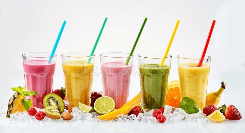 Cinco vidros altos de batidos de fruta tropicais foto de stock royalty free