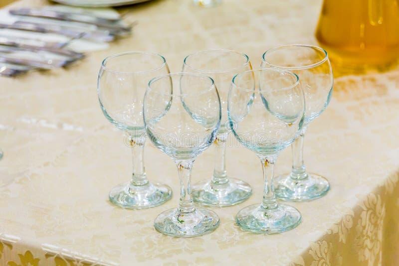 Cinco vidros de vinho vazios na tabela Servindo em um banquete, abastecendo fotografia de stock royalty free