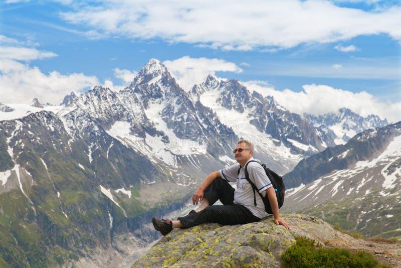 Cincuenta años de turistas que se sientan en una roca contra cumbres de la montaña imagen de archivo