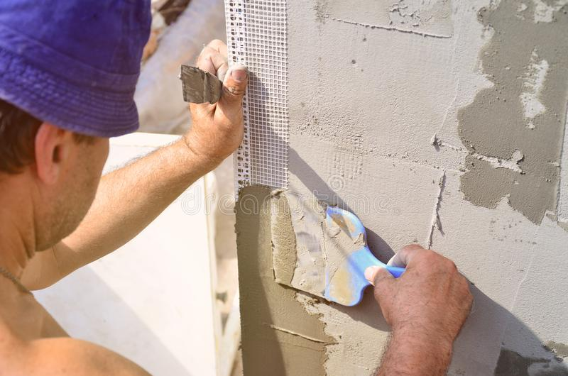Cincuenta años del trabajador manual con la pared que enyesa las herramientas que renueva la casa fotografía de archivo