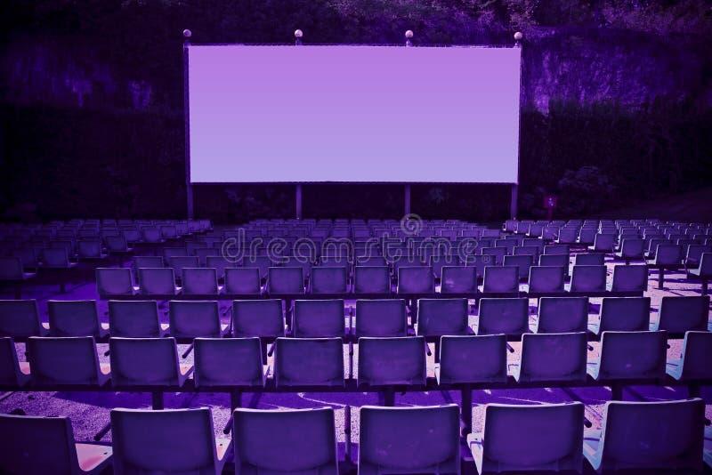 Cine al aire libre con sillas y pantalla de proyección blanca en la naturaleza - Imagen de tono con espacio de copia imagen de archivo
