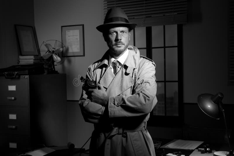Cine negro: detective que celebra un revólver y una presentación fotografía de archivo libre de regalías