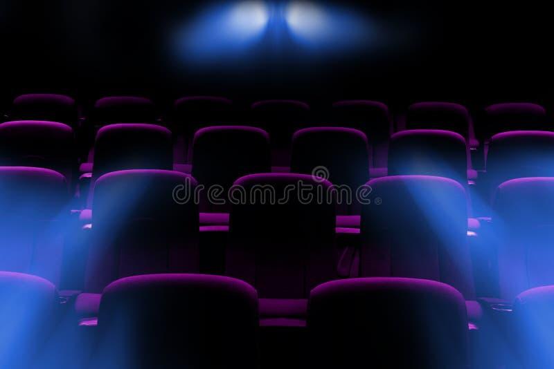 Cine vacío con los asientos púrpuras con la luz de la llamarada del proyector foto de archivo libre de regalías