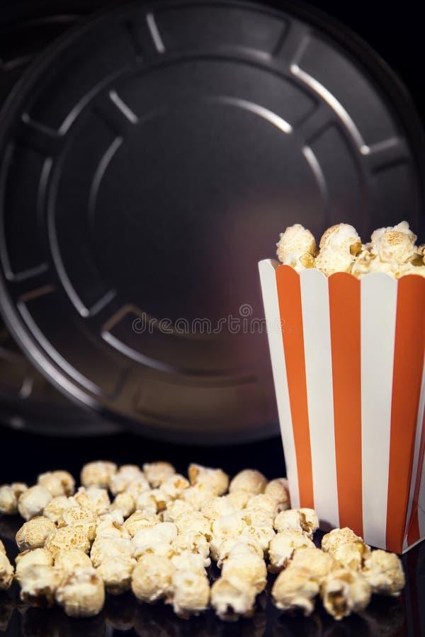 Cine y cine, carrete y palomitas delante del negro imagen de archivo