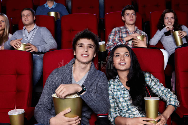 Cinema. Young people are closely watching a movie at the cinema