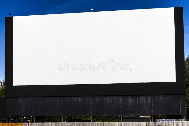 Cinema all'antica del drive-in con lo schermo bianco in bianco per lo spazio della copia o la pubblicità II immagine stock