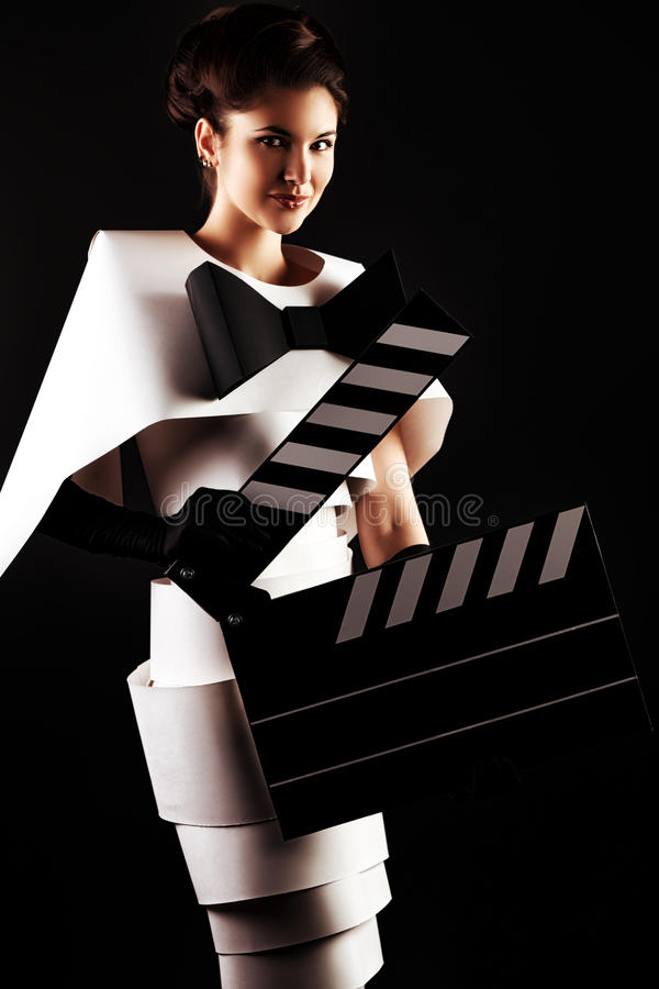 Cinema clap. Art fashion photo of a gorgeous woman in paper dress holding cinema clap. Black and white royalty free stock photography