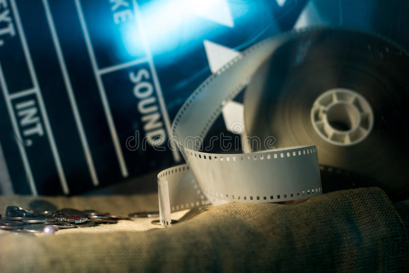 Cinema clapper and video film negative movie on a rough cloth. Coins lying on the fabric stock photography