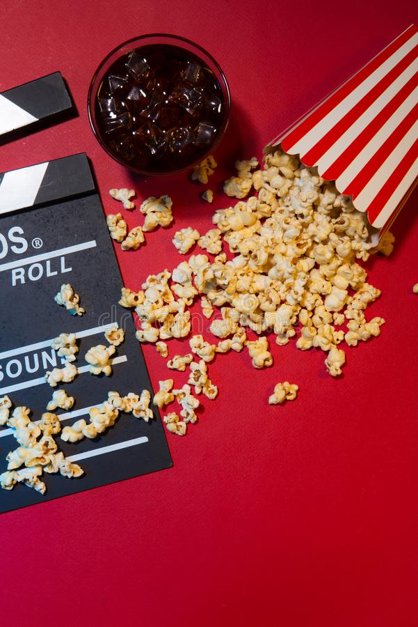 Cinema concept. Clapperboard, ticket and popcorn on red background stock photography