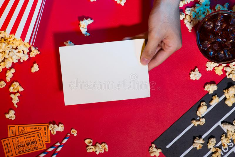 Cinema concept. Clapperboard, ticket and popcorn on red background royalty free stock image