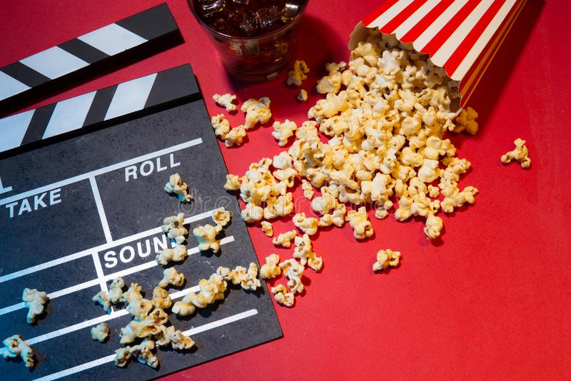 Cinema concept. Clapperboard, ticket and popcorn on red background royalty free stock photos
