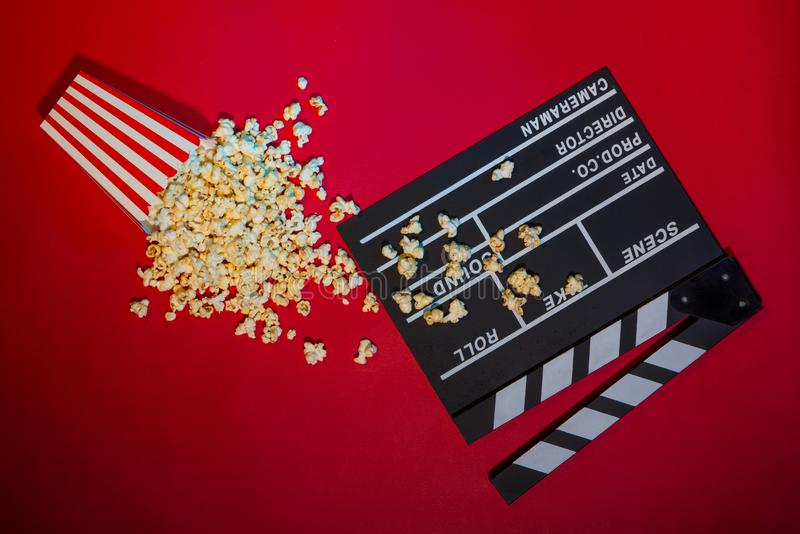 Cinema concept. Clapperboard, ticket and popcorn on red background stock images