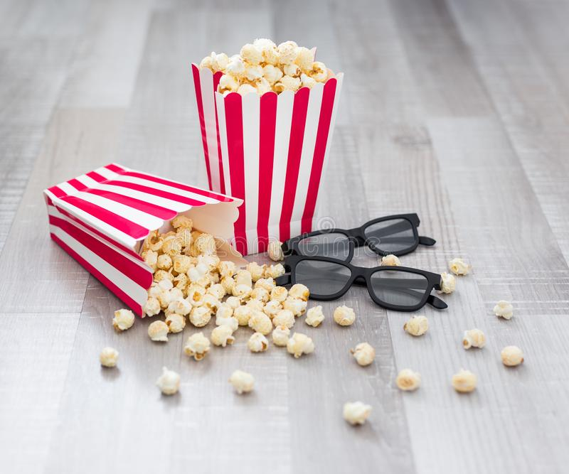Cinema concept - close up of 3d glasses and popcorn in striped boxes on wooden background royalty free stock photography