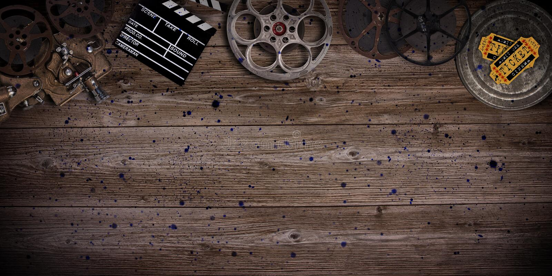Cinema concept of vintage film reels, clapperboard and projector. Cinema concept of vintage film reels, clapperboard and projector on old wooden background royalty free stock photos