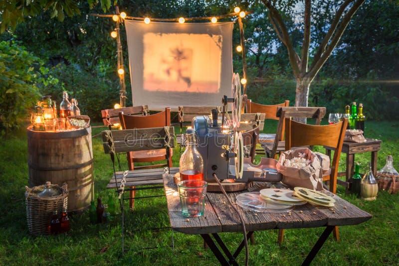 Cinema do ar livre com o projetor retro no jardim do verão imagem de stock