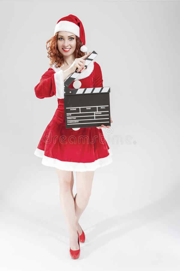 Cinema and Film Production Concept and Ideas. Full Length Portrait of Smiling Female Santa Helper Girl with Actioncut or. Clapperboard Posing Against White royalty free stock images