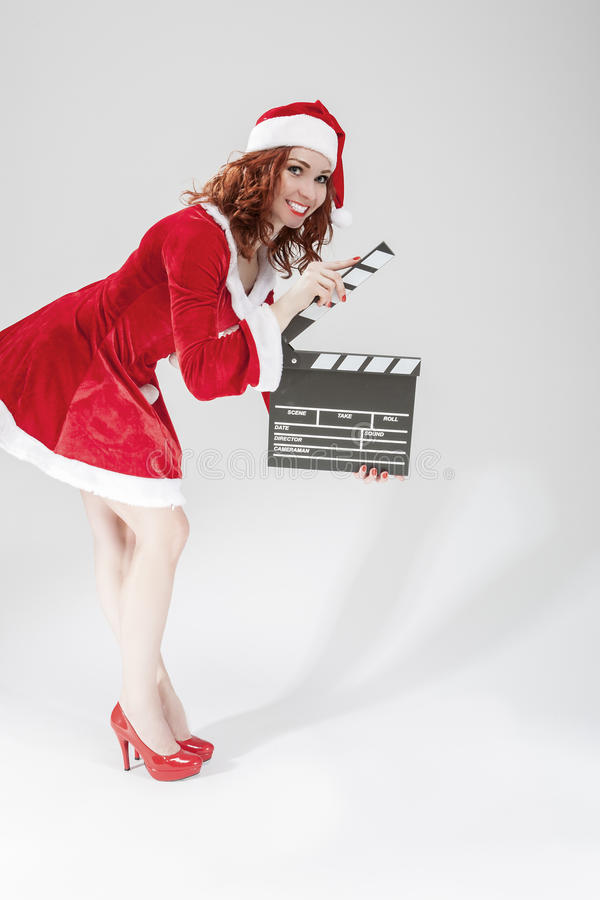 Cinema and Film Production Concept and Ideas. Happy Smiling Female Santa Helper Girl with Actioncut or Clapperboard Posing. Against White Background.Vertical stock image