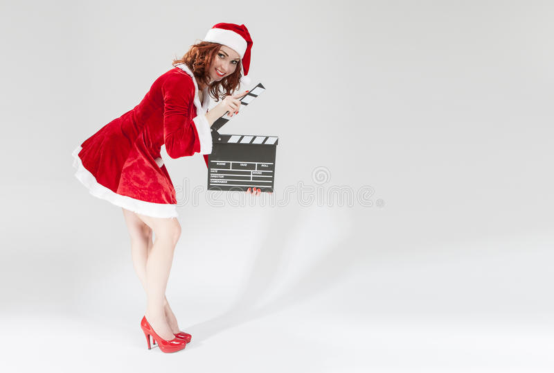 Cinema and Film Production Concept and Ideas. Happy Smiling Female Santa Helper Girl with Actioncut or Clapperboard Posing. Cinema and Film Production Concept stock photo