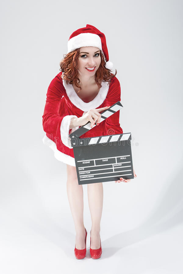 Cinema and Film Production Concept and Ideas. Portrait Of Smiling Female Santa Girl with Clapperboard Posing Against White. Cinema and Film Production Concept royalty free stock image