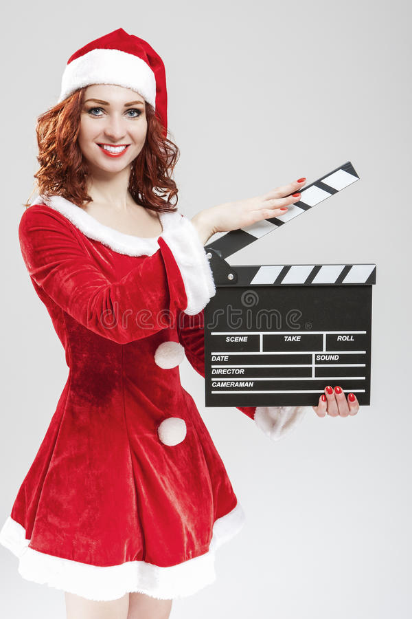 Cinema and Film Production Concept and Ideas. Portrait Of Smiling Female Santa Girl with Clapperboard Posing Against White. Background.Vertical Shot stock photo