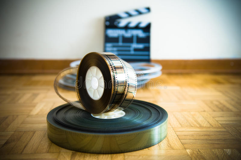 Cinema film reel and out of focus movie clapper board. 35 mm cinema film reel and out of focus movie clapper board in background on wooden floor stock images
