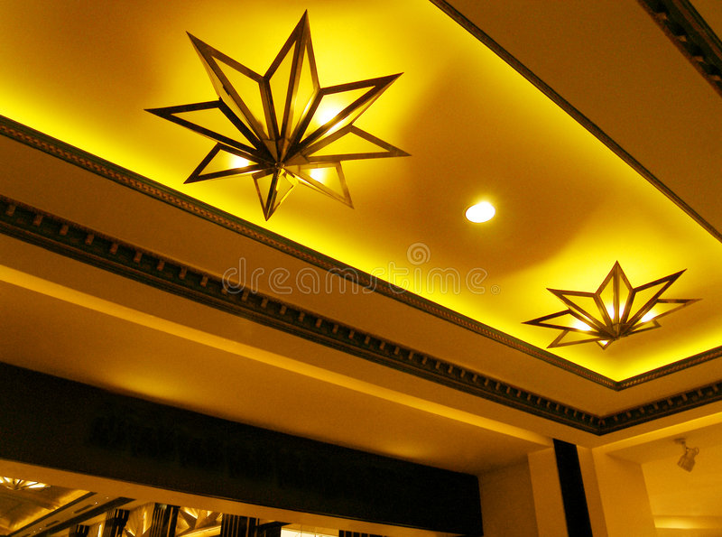 Cinema lobby entrance. An interior shot of the entrance of a cinema movie house lobby or foyer, with grand golden color decor and finishing. Ceiling lights in stock photography