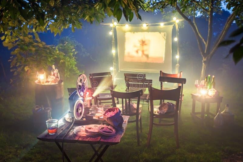 Cinema pequeno com o projetor retro no jardim do verão imagens de stock royalty free
