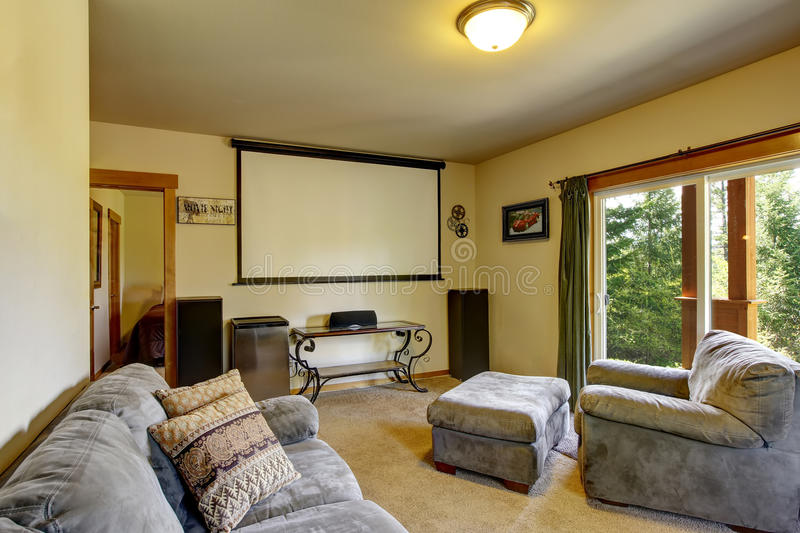 Cinema room in American house with projector screen on the wall royalty free stock photos
