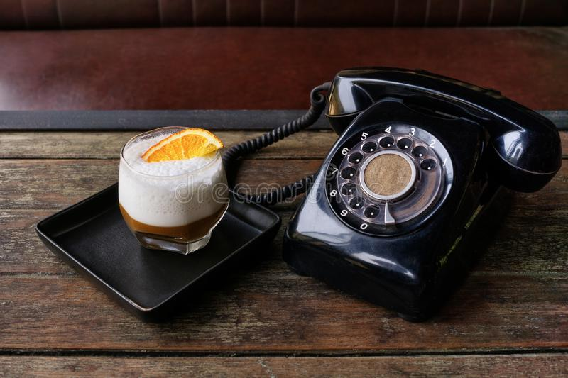 Cinema style photo of black dial phone and coffee cocktail with orange peel on wooden table. Luxury, creative background, Old fash stock photography