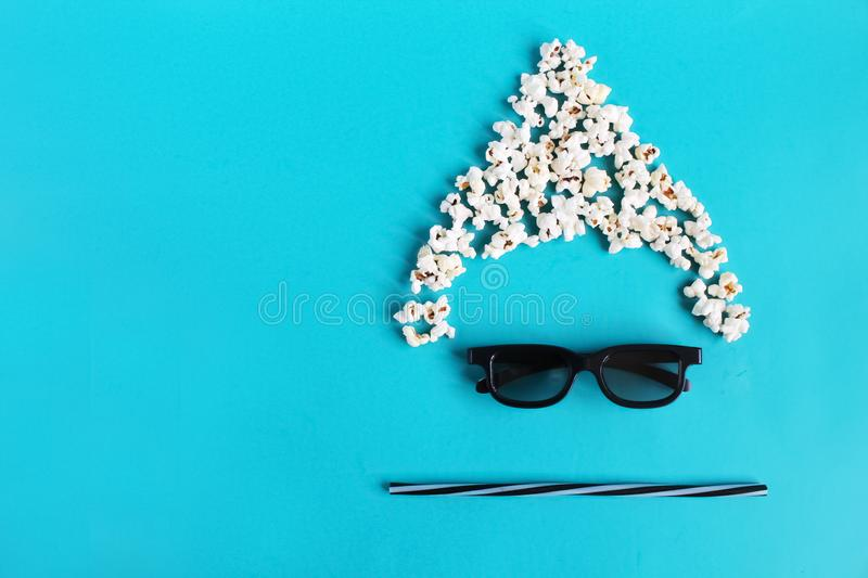 Cinema time on blue paper background. Abstract fun image of viewer, 3D glasses, popcorn. Concept cinema movie and entertainment. Flat lay composition with copy royalty free stock image