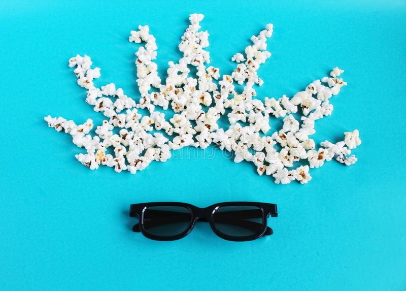 Cinema time on blue paper background. Abstract image of movie viewer, 3D glasses, popcorn. Concept cinema movie and entertainment. Flat lay composition with stock photos