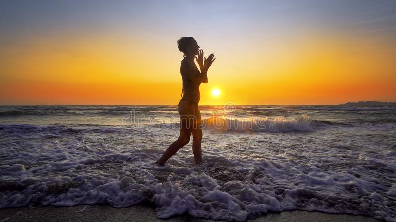 Cinematic shot of woman walking on water at sunset royalty free stock photos