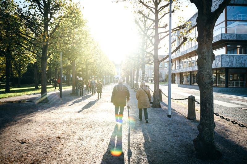 Cinematicscène met vreedzame zonsondergang en mensen die op steeg Schloss Bezirk lopen royalty-vrije stock foto