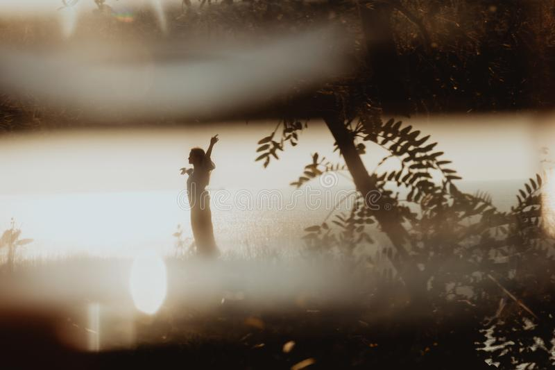 Cinematographic view on woman silhouette in dress dancing on coast in sunrise. A cinematographic shot of woman silhouette in dress dancing on coast in sunrise royalty free stock photo