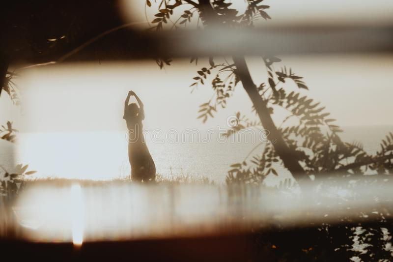 Cinematographic view on woman silhouette in dress dancing on coast in sunrise. A cinematographic shot of woman silhouette in dress dancing on coast in sunrise royalty free stock photography