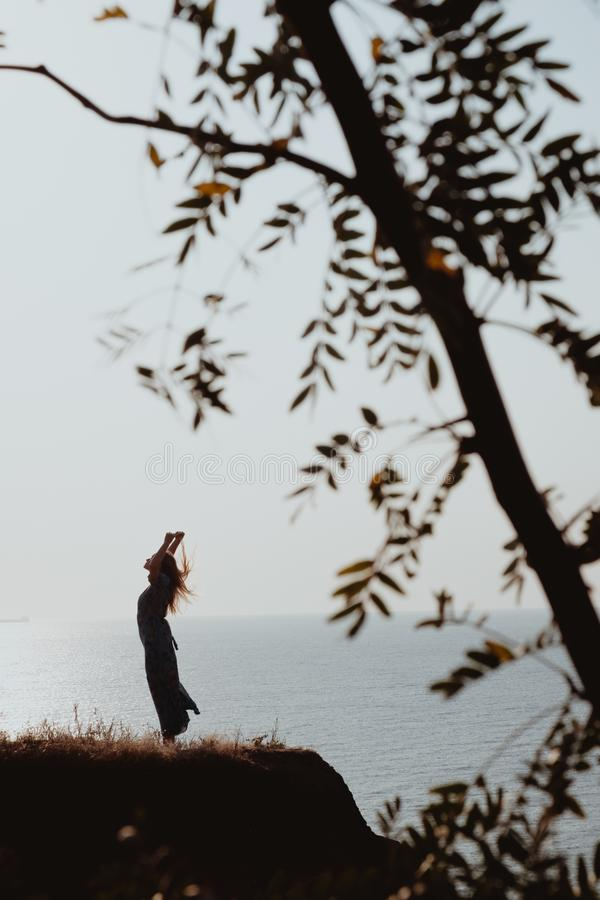 Cinematographic view on woman silhouette in dress dancing on coast in sunrise. A cinematographic shot of woman silhouette in dress dancing on coast in sunrise royalty free stock photos