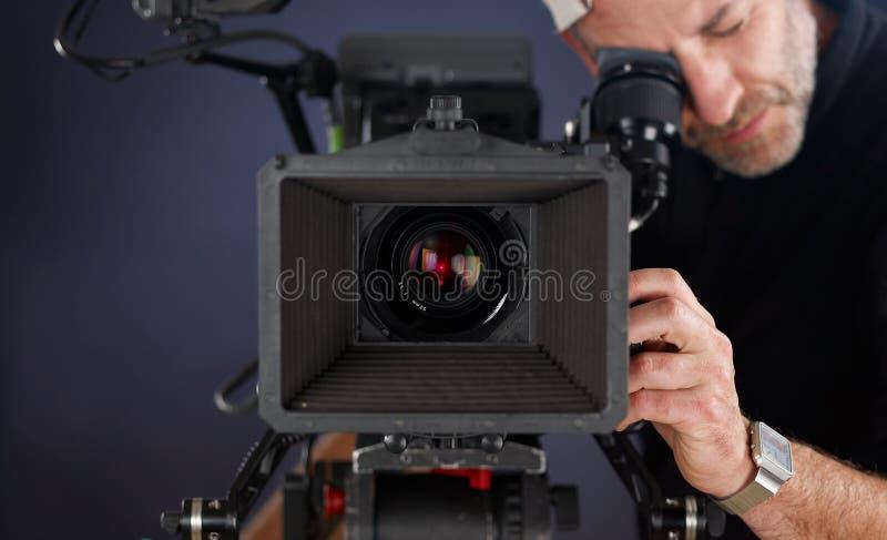 Cineoperatore che lavora con una macchina fotografica del cinema immagini stock libere da diritti