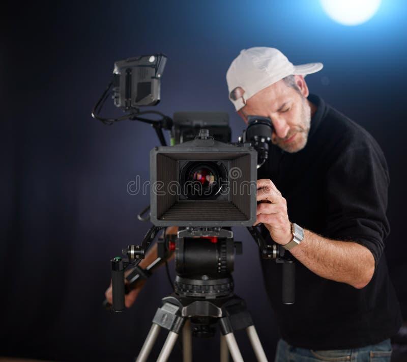 Cineoperatore che lavora con una macchina fotografica del cinema immagine stock libera da diritti