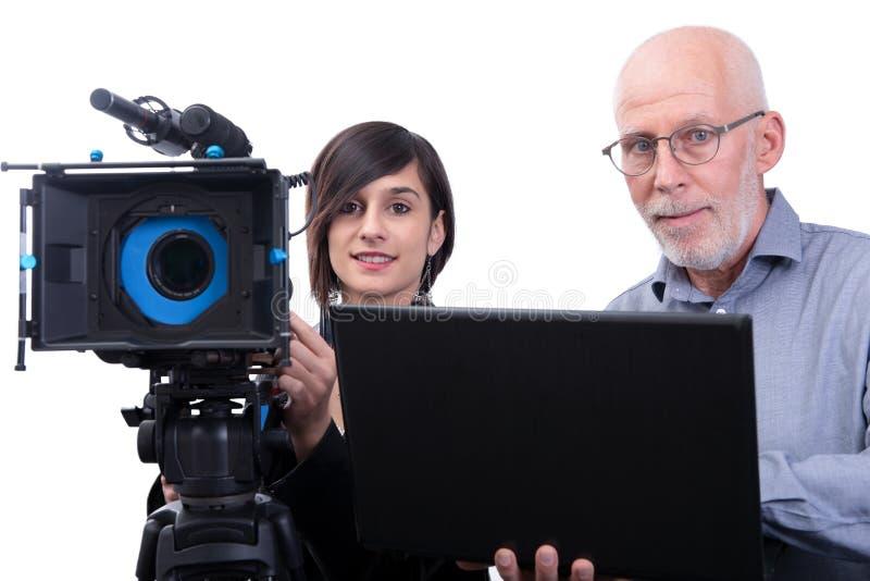 Cineoperatore e una giovane donna con una cinepresa DSLR su bianco fotografia stock
