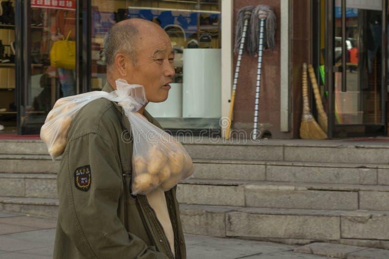 Cinese con le borse delle patate sulla sua spalla immagini stock