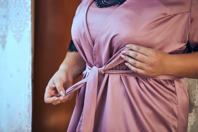 Cinghia dei legami della ragazza sul suo abito che sta finestra vicina, donna che si prepara prima della cerimonia di nozze fotografie stock