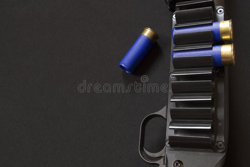Cinghia di cartuccia provvista di cardini, innesco e tre cartucce del fucile da caccia fotografie stock