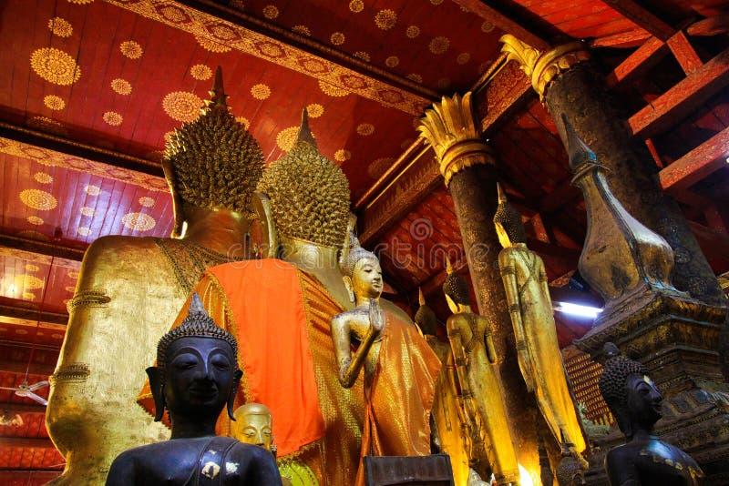 CINGHIA DI LUANG PRABANG WAT XIENG, LAOS - 17 DICEMBRE 2017: Statue di Buddha dentro il tempio illuminato da luce solare naturale fotografie stock