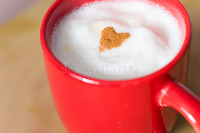 Cinnamon heart on the top of a latte stock photography