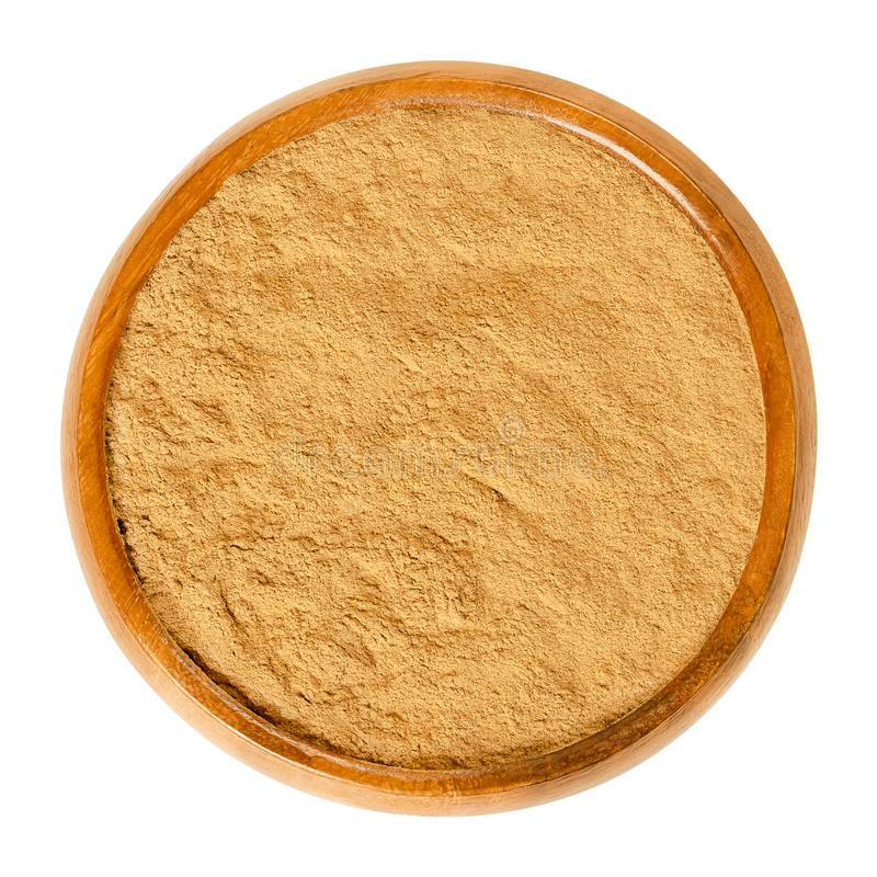 Cinnamon powder in wooden bowl over white royalty free stock photography