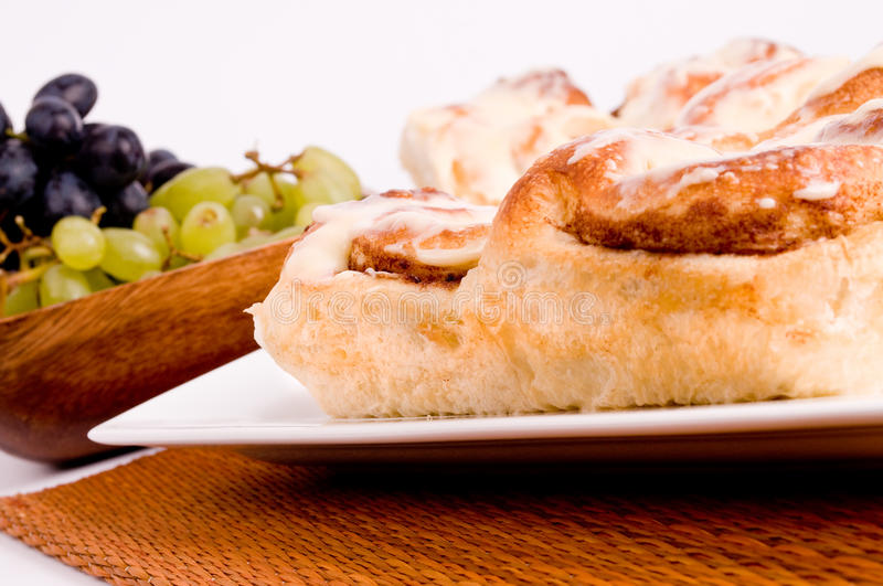 Cinnamon rolls. A plate of fresh baked cinnamon rolls with a bowl of grapes royalty free stock photo