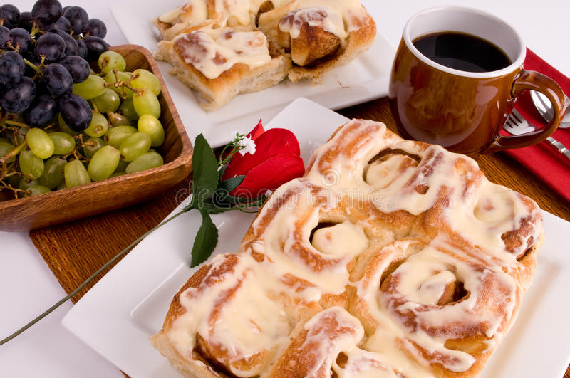 Cinnamon rolls. A plate of fresh baked cinnamon rolls with a bowl of grapes and a cup of coffee stock image