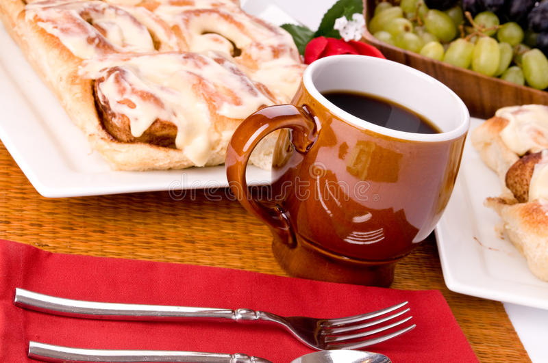 Cinnamon rolls. A plate of fresh baked cinnamon rolls with a bowl of grapes and a cup of coffee stock photos