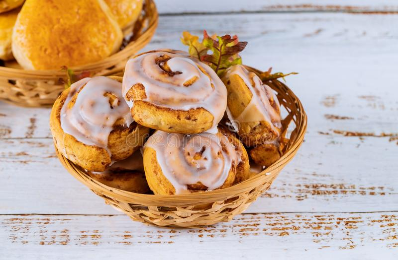 Cinnamon rolls with glaze on the top. In wooden plate, dessert, leaf, food, sweet, fall, breakfast, pastry, baked, bun, snack, sugar, homemade, bakery, fresh royalty free stock photo